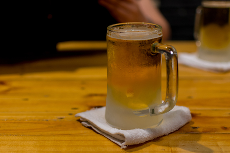 Beer in mug glass with ice and froth on a wood table Stock Photo