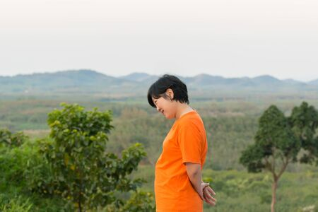 plump: Asia woman plump body in orange T-shirt posing and smile at mountain view when travel Stock Photo
