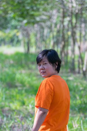 plump: Asia woman plump body at rubber tree in row at a rubber tree plantation natural latex. Stock Photo