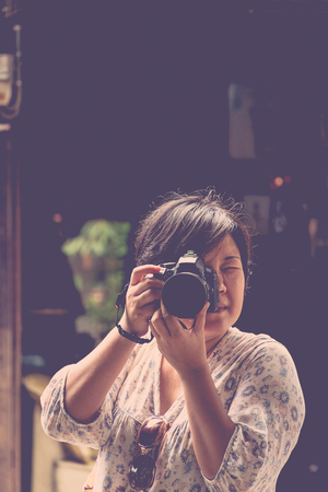 plump: Asia woman plump body in colorful dress take a photo by her camera at old town when travel , process in vintage style