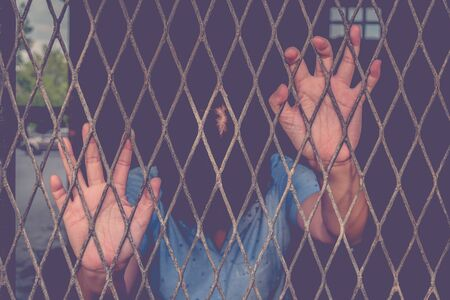inmate: Hands of the woman on a steel lattice close up , process in vintage style Stock Photo