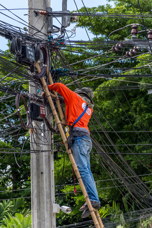 linemen: Bangkok, Thailand - June 26, 2016 : Unidentified worker working to install electric line by scaffolding on pickup truck at Bangkok Thailand.
