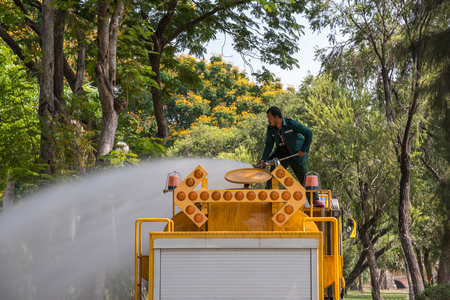 Bangkok, Thailand - March 25, 2017 : Unidentified worker gardener of public park working for watering the lawn plants and trees  by water tanker truck in city park Editorial