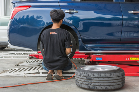 disassembly: Bangkok, Thailand - March 9, 2017 : Unidentified car mechanic or serviceman disassembly and checking a car alloy wheel for fix and repair suspension problem at car garage or repair shop