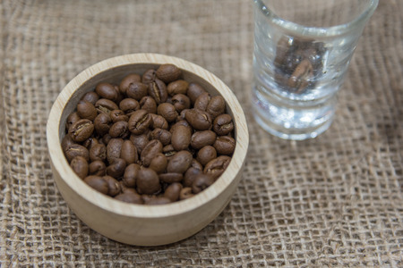 Coffee beans and roasted coffee beans in wooden bowl on the sack cloth