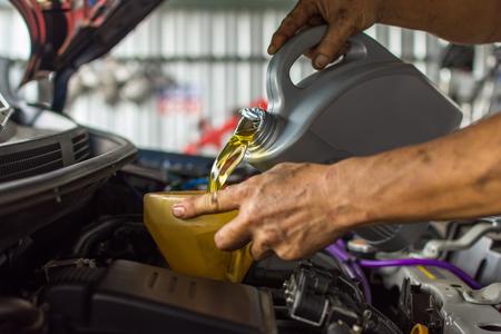 dirty car: Car mechanic fills a fresh lubricant engine oil at car garage for maintenance a car Stock Photo