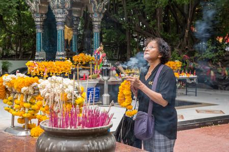 intend: Bangkok, Thailand - March 28, 2017 : Unidentified Thai buddhism people in buddhist pray for benefaction worship by incense and garland to Buddha or spirit-house at shrine or Thai temple (Wat Thai) Editorial