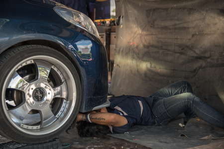 damage control: Bangkok, Thailand - April 9, 2017 : Unidentified car mechanic or serviceman checking a car engine for fix and repair problem at car garage or repair shop