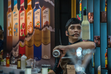 bartending: Bangkok, Thailand - March 19, 2017 : Unidentified bartender or barman mixing a drink for show and service at restaurant Editorial