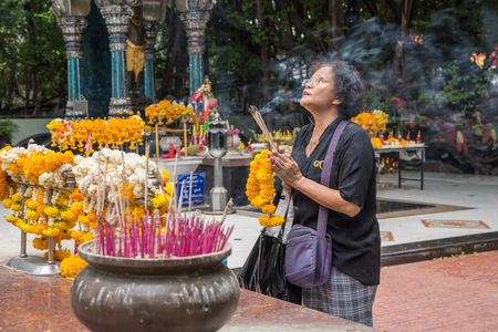 Bangkok, Thailand - March 28, 2017 : Unidentified Thai buddhism people in buddhist pray for benefaction worship by incense and garland to Buddha or spirit-house at shrine or Thai temple (Wat Thai) Editorial