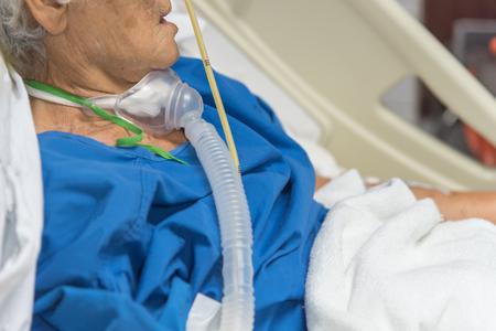 Patiënt Aziatische oudere vrouwen 80's gebruiken tracheostomie ventilator voor ademhulp op bed in het ziekenhuis.