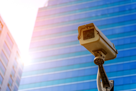 Security camera (CCTV) for safety on blue sky and city background Stock Photo