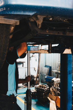 disassembly: Car mechanic or serviceman checking a car engine for fix and repair problem at car garage or repair shop Stock Photo