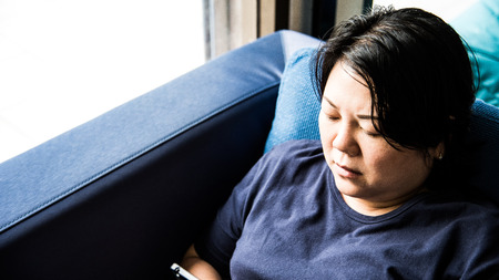 suspicion: Asian women 40s white skin and plump body in blue dress holding smartphone have a doubt and think gesture on a blue sofa near window Stock Photo