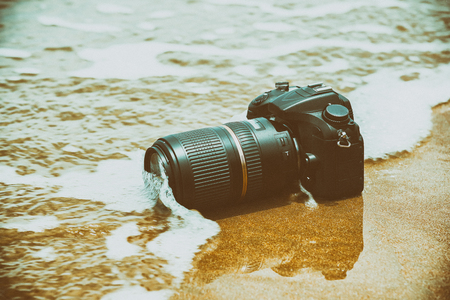 Photographer demo waterproof for DSLR camera and tele lens by wet from water sea wave at beach when travel and test using in the extreme environment