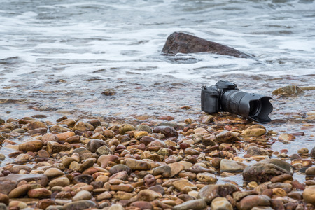 immersed: DSLR camera with telephoto lens on a beach it wet from water sea wave when travel