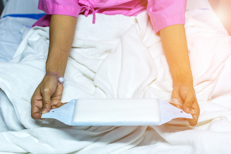 sanitary napkins and tampons: Patient asian woman with adhesive plaster on hand using sanitary napkin for menstruation on patient bed in the hospital