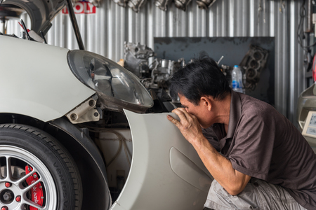 disassembly: Bangkok, Thailand - May 5, 2017 : Unidentified car mechanic or serviceman checking a car engine for fix and repair problem at car garage or repair shop