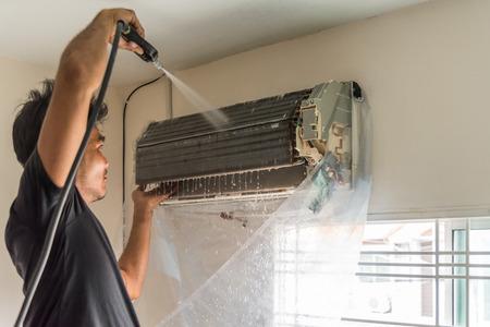 Bangkok, Thailand - 22 juli 2017: Unidentified werknemer voor het reinigen van bobijnkoeler van airconditioner door water voor het reinigen van een stof op de muur in de klant thuis wanneer onderhoudsservice