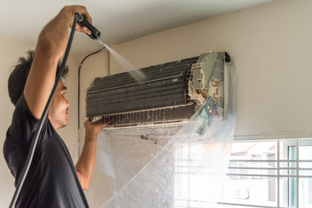 Bangkok, Thailand - July 22, 2017 : Unidentified worker to cleaning coil cooler of air conditioner by water for clean a dust on the wall in customer home when maintenance service Banco de Imagens - 83842472