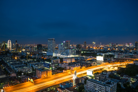 Bangkok, Thailand - May 15, 2017 : Cityscape and light of night road in long exposure with billboard from skyscraper of Bangkok. Bangkok is the capital and the most populous city of Thailand.