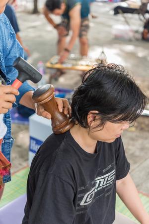 방콕, 태국 - 우리 모두의 2017 년 7 월 28 일 : 정체 불명 된 태국 여자 서비스 태국어 나무 망치로 통증 및 통증 치료에 걸릴. 야외 정원에서 서비스가 제 에디토리얼