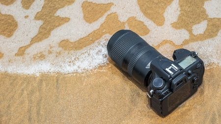 when: DSLR camera with telephoto lens on a beach it wet from water sea wave when travel