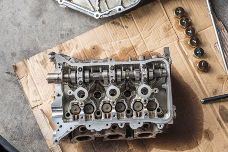 dismantled: Disassembled car dirty engine close-up to engine parts and cylinder head at car garage