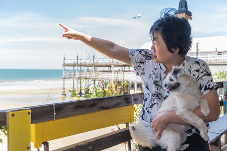 Asian women point finger to sky with sunlight and the dog so cute mixed breed with Shih-Tzu, Pomeranian and Poodle at beach and the sea when travel Stock Photo