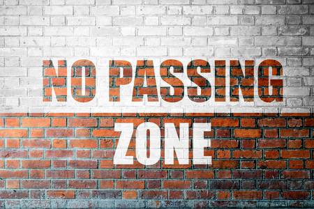 Red Brick wall texture background with a word No Passing Zone