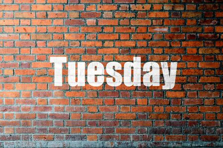 Red Brick wall texture background with a word Tuesday Stock Photo