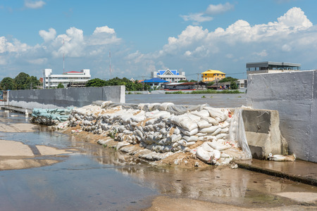 Ang Thong, Thailand - October 21, 2017 : Dams created from sand bags. To prevent flooding caused by heavy rain The water in the river is so high that it is higher than the road in city. 版權商用圖片 - 91155365