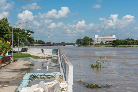 Ang Thong, Thailand - October 21, 2017 : Dams created from sand bags. To prevent flooding caused by heavy rain The water in the river is so high that it is higher than the road in city. Editorial