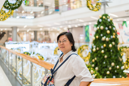Asian woman 40s white skin plump body with backpack waiting in department store or shopping mall with pine tree in merry christmas and new yaer celebration