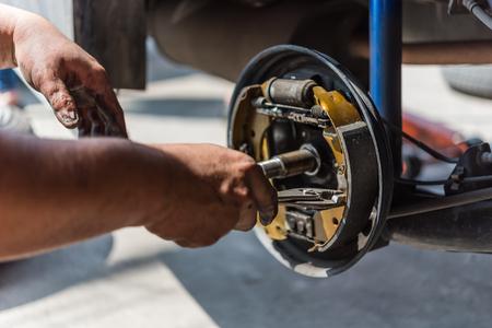 Automechaniker oder -soldiker, die eine Trommelbremse und Asbestbremsbeläge überprüfen, ist es ein Teil des Autogebrauchs für Halt das Auto für Sicherheit am Hinterrad dieses ein neues Ersatzteil für Reparatur an der Autogarage