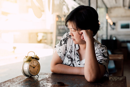 Asian woman 40s white skin plump body in black and white shirt have a bored and unhappy gesture between waiting something in a coffee shop cafe with a clock vintage style