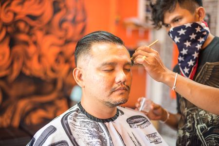 Bangkok, Thailand - April 25, 2017 : Unidentified Thai man barber haircut a man customer in fashion vintage hairstyle at barbershop