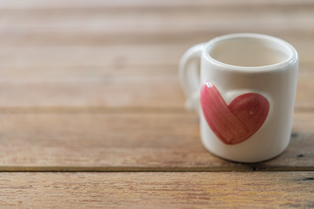 Ceramic white cup with heart shape sweet pink color on wooden floor with copy space in Valentines Day, Wedding or Romantic Love concept