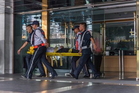 Bangkok, Thailand - 30 november 2017: Veel werkende mensen paraatheid voor brandoefening of andere ramp door beweging letsel patiënt op ruggengraat bord op kantoor in Bangkok Thailand