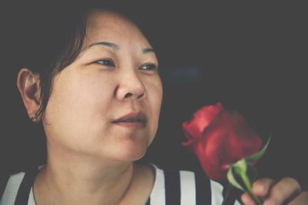 Asian woman 40s plump body smelling red rose flower nature beautiful flowers for valentines from the garden in Valentines Day, Wedding or Romantic Love Valentine concept