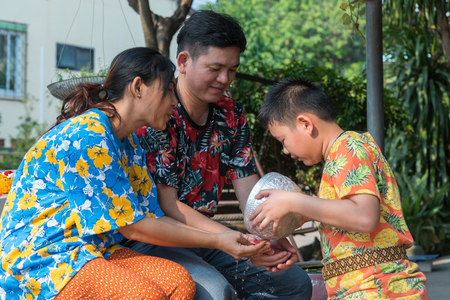 Ang Thong, Thailand - April 13, 2018 : Unidentified Asian young bathe with respect to parents by water have a jasmine and rose flower and aromatherapy in water in water bowl in Songkran Festival
