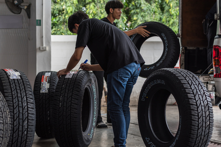 Bangkok, Thailand - August 31, 2017 : Unidentified car mechanic or serviceman disassembly and checking a car alloy chrome wheel for fix and repair suspension problem at car garage or repair shop