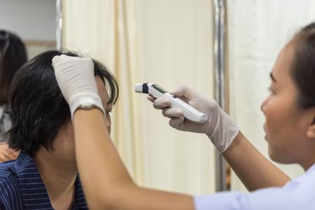 Bangkok, Thailand - 29 juni, 2018: Niet-geïdentificeerde Thaise vrouw gezondheidscontrole meet koortsniveaus door digitale infrarood thermometer elk jaar in het ziekenhuis door het ministerie van Volksgezondheid.