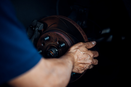 Car mechanic or serviceman checking a disc brake and asbestos brake pads it's a part of car use for stop the car for safety at front wheel this a new spare part for repair at car garage