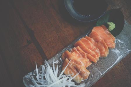 Japanese food delicacy consisting sashimi salmon of very fresh raw salmon fish sliced into thin pieces serving with radish sliced in japanese restaurant