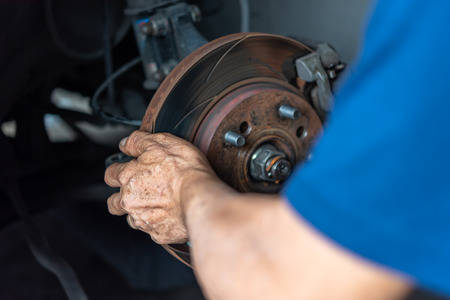 Car mechanic or serviceman checking a disc brake and asbestos brake pads its a part of car use for stop the car for safety at front wheel this a new spare part for repair at car garage