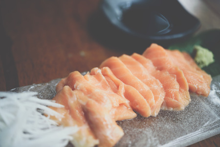 Japanese food delicacy consisting sashimi salmon of very fresh raw salmon fish sliced into thin pieces serving with radish sliced in japanese restaurant