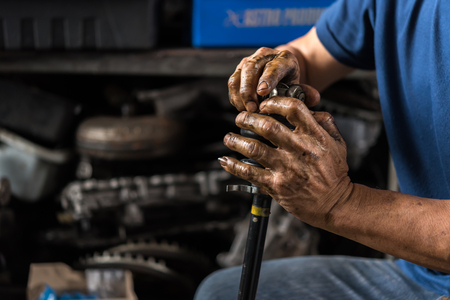 Car mechanic or serviceman disassembly and checking a car alloy chrome wheel for fix and repair suspension problem at car garage or repair shop