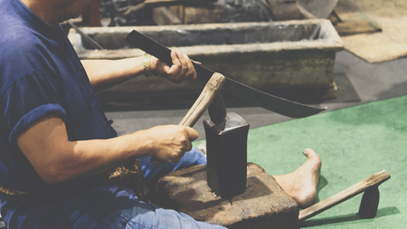 Blacksmith or professional knife hit a knife or sword for show how to make traditional sword from iron.