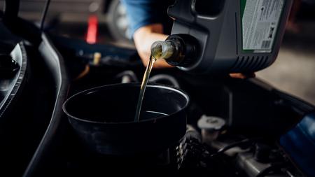 Car mechanic or serviceman fills a fresh lubricant engine oil at car garage for repair or maintenance a car